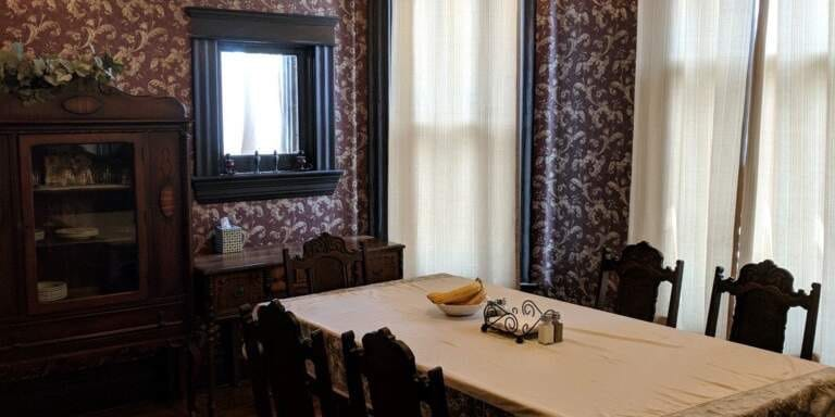 A dining room with maroon and gold wallpaper and seating for six
